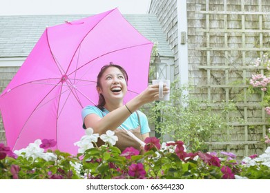 Asian woman with umbrella holding mug out in rain