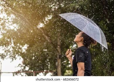 Asian woman under an umbrella in the rain.