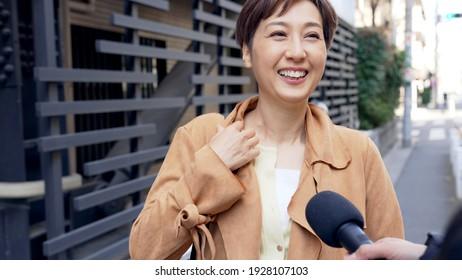Asian woman undergoing a street interview.