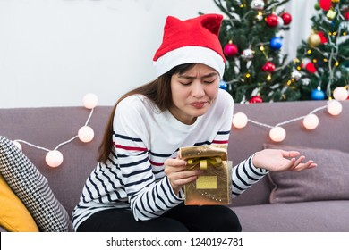 Asian woman upset when open gold xmas gift box at holiday party on sofa,boredom Christmas party present