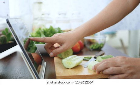 Asian woman use finger slide on tablet screen prepare ingredients for cooking follow cooking online video clip on website. cooking content on internet technology for modern lifestyle concept