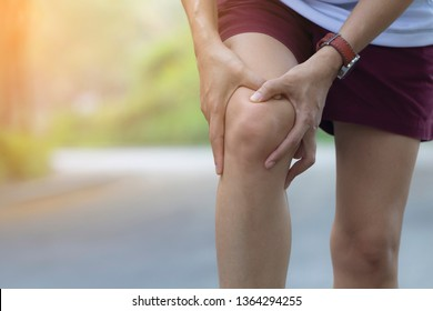 Asian woman use hands hold on her knee injury while running on road in the park, Injury from workout concept.
