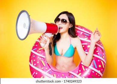 asian woman use loudspeaker wearing bikini swimsuit with donut swim ring