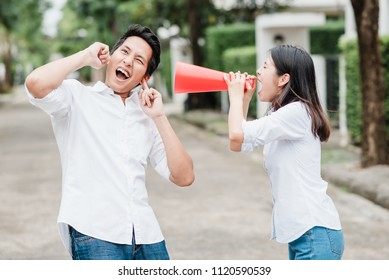 Asian woman use megaphone screaming and shouting to Asian man outdoor