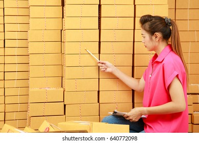 Asian woman use pencil counting parcel boxes in her own job shopping online business at home in front of high stack of parcels