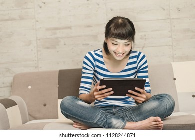 Asian woman use a tablet pc at home