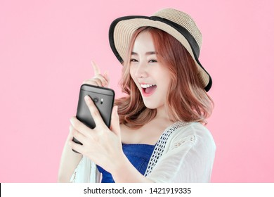 Asian woman use video call with smartphone, summer holiday clothing, pink background