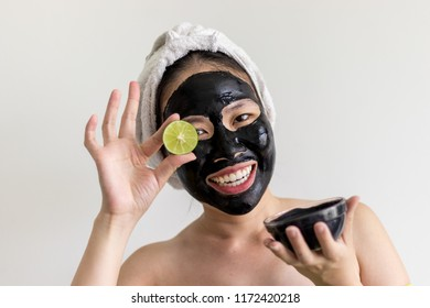 An asian woman using activated black charcoal and yogurt mask on her face for deep cleaning the skin, beauty and skincare product for acne and blackheads removal