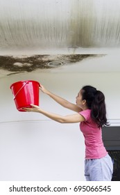 Asian woman using a bucket for collecting water leaking from the ceiling
