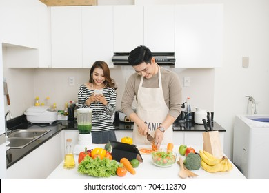 Asian woman using cell phone while a man prepares a meal
