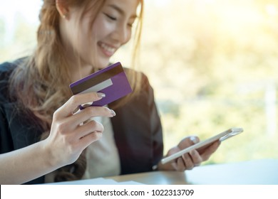 Asian woman using credit card shopping online with smartphone at coffee shop - Online payment concept.