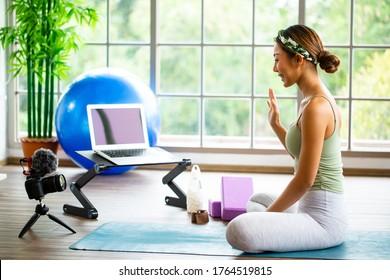 Mujer asiática que usa una cámara réflex digital para transmitir en vivo enseñar yoga en línea en la sala de estar. Los tailandeses sonríen de la práctica de tutoría de trabajo a la sala de clases en línea para los que se quedan en casa.