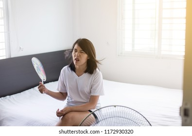 Asian woman using fan because suffering heat wave and sitting on bedroom,Hot with high thermometer