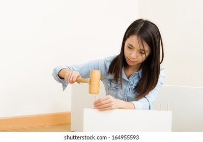 Asian woman using hammer for assembling new furniture