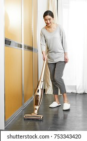 Asian woman using a handheld vacuum cleaner to clean the bedroom wood floor at home