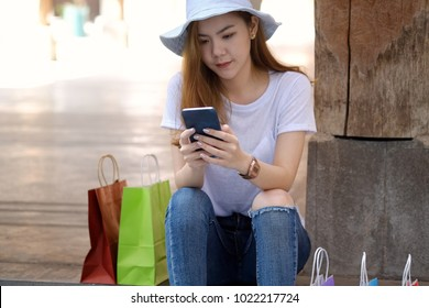 ?Young asian  woman using her cellphone while sitting in front of a building with a bunch of shopping bags