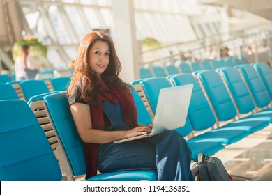 Asian woman using a laptop to check email or social network or internet at the international airport to travel on weekends.