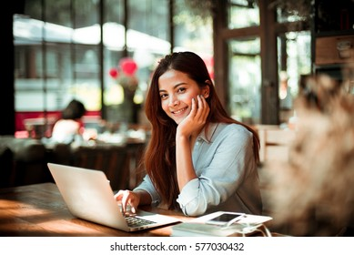 Asian woman using laptop in coffee shop cafe vintage color
