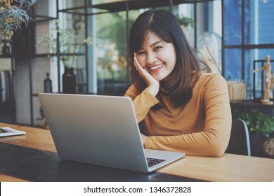 Asian woman using laptop computer in coffee shop cafe