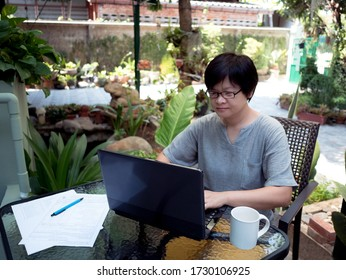 asian woman using laptop for meeting online , with documents and white coffee cup  in garden at home, trees on blurred background. work from home concept.