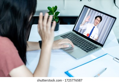 Asian woman using laptop, smartphone and tablet to work from home and video call online via internet with customer from home. Cozy office workplace. Work from home or E-Learning concept.