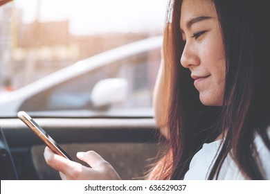 An Asian woman using and looking at smart phone in a car on the road