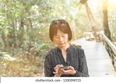 Asian woman using mobile at the outdoor