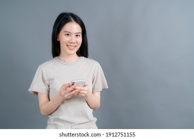 Asian woman using mobile phone applications, enjoying communicating distantly online in social network or shopping isolated on grey background