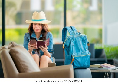 Asian woman using mobilephone at the airport in the waiting room. Asian woman typing on smartphone in lounge area. Portrait of woman sitting and holding passport with luggage.