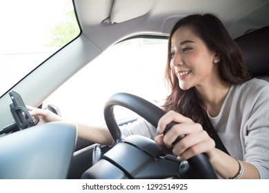 Asian woman using phone and sending a message behind the wheel, Female driving a car with using navigation or application on smartphone, Smart technology concept
