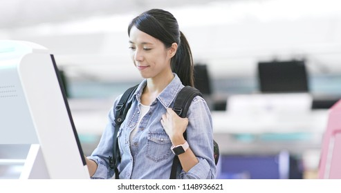 Asian Woman using selfie check in machine in the airport