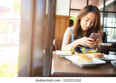 Asian woman using smart phone in restaurant