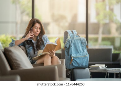 Asian woman using smartphone at airport terminal sitting with luggage suitcase and backpack for travel in vacation summer relaxing waiting for airplane arrival and reading book with laptop on table.