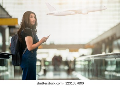 Asian woman using smartphone in the airport and airplane on background, travel, vacations and active lifestyle concept
