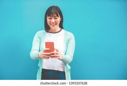 Asian woman using smartphone with blue background - Happy chinese girl having fun with new trends technology - Fashion, tech and millennial generation activity - Focus on face