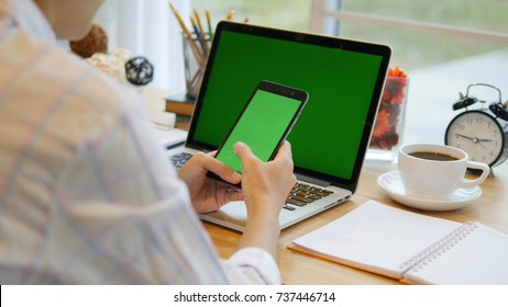 Asian woman using smartphone with green screen on the table with laptop computer Chroma key. Close-up shot of woman's hands holding mobile phone.