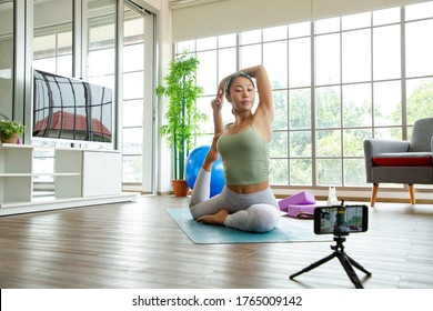 Asian woman using smartphone for Live stream yoga online classroom. Thai people wear green sport shirt and exercise in living room.