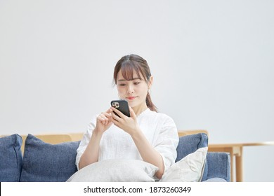 Asian woman using the smartphone on the sofa - Shutterstock ID 1873260349