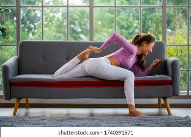 Mujer asiática que usa un smartphone para leer y verificar el estado y entrenar yoga en el sofá. Gente tailandesa sonriendo y relajándose en casa.
