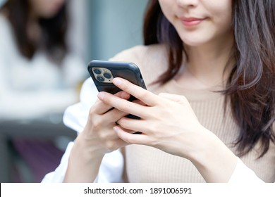 Asian woman using the smartphone at the sidewalk cafe, no face