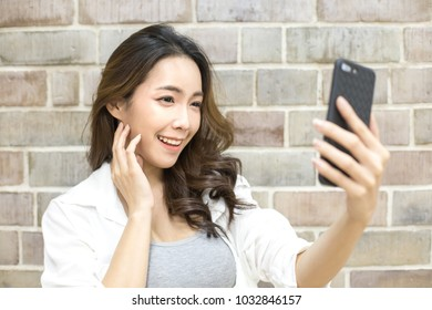 Asian woman using smartphone with smiling at wall background. Woman using smartphone for selfie or video call in social media. People with technology concept.