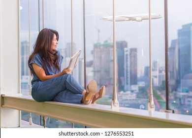 Asian woman using tablet computer and relaxing while sitting near window glass with airplane and business buildings on background.