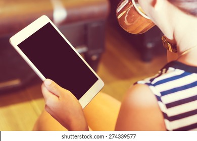 Asian woman using tablet computer in cafe drinking coffee. Focus on tablet. (Vintage process tone)