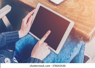 Asian woman using tablet computer in coffee shop with Vintage tone.