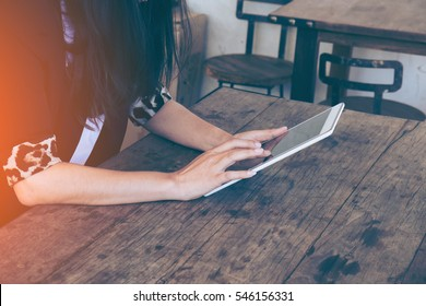 Asian woman using tablet on table in coffee shop with vintage toned.