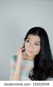 Asian woman using telephone and thinking