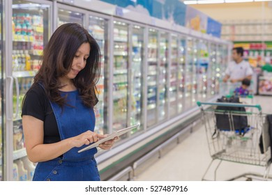 Asian woman using and touch screen tablet over blurred people and aisle milk yogurt frozen food freezer background in supermarket. (advertise concept, lens blur effect)