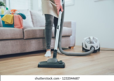 asian woman using vacuum cleaner in the living room. housekeeper wearing pink protective rubber gloves cleaning the wooden floor in the house. full of clean supplies in bucket on comfortable sofa