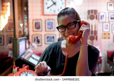 A Asian woman using the vintage telephone.