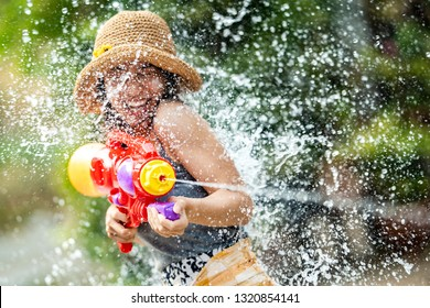 Asian woman are using water guns play in the Songkran festival